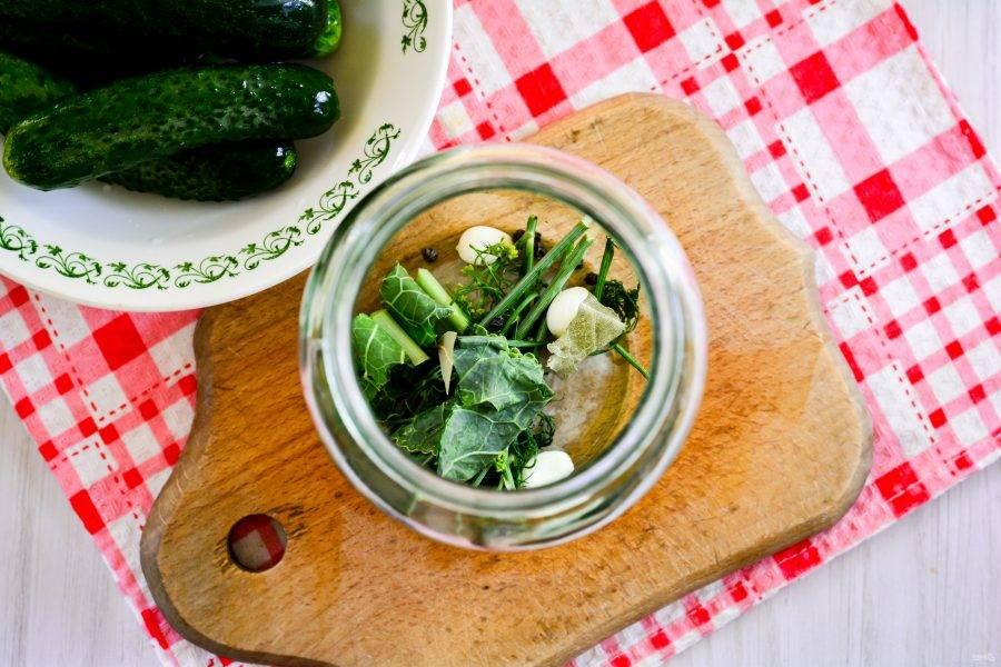На дно простерилизованных банок выложите специи — зубчики чеснока, перец горошком, лавровый лист и зелень. Выложите несколько веточек укропа, можно сушеного, и нарезанный листочек хрена. Хрен придаст огурцам хрустящий вкус и сохранит упругость овощей.