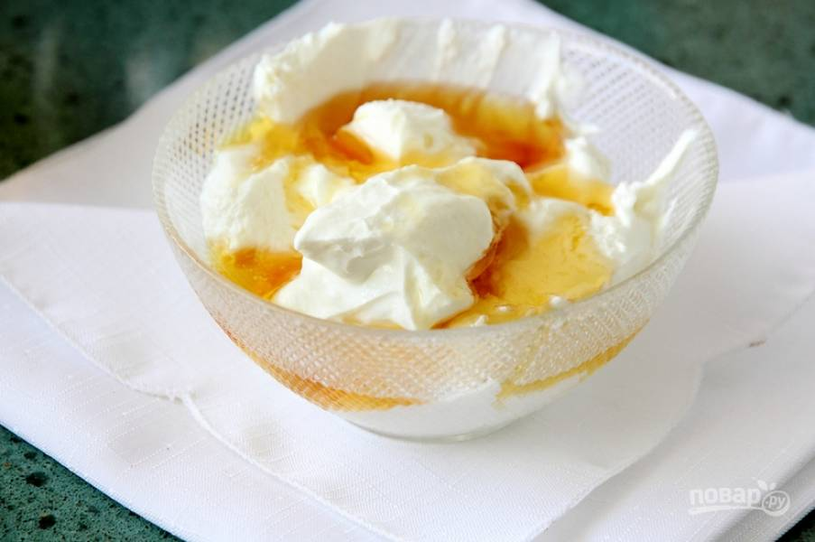 По одному вбейте яичные желтки, продолжая взбивать. Перемешайте мед с творогом. Соедините обе массы, аккуратно перемешав их.
