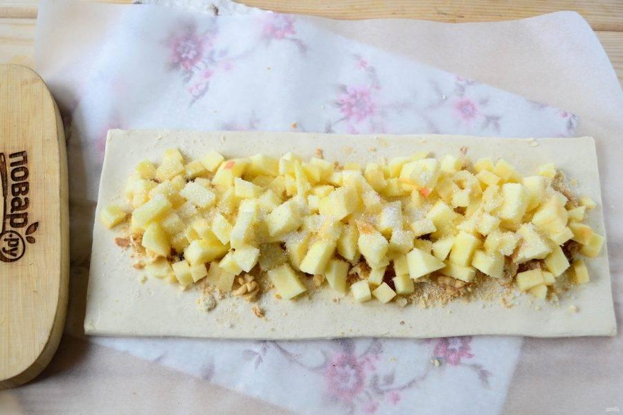 Яблоки очистите, удалите сердцевину. Порежьте яблоки на мелкие кубики. Выложите яблоки на тесто, также оставляя бортики по 1,5 см. Яблоки сверху присыпьте оставшимся сахаром и лимонной цедрой.