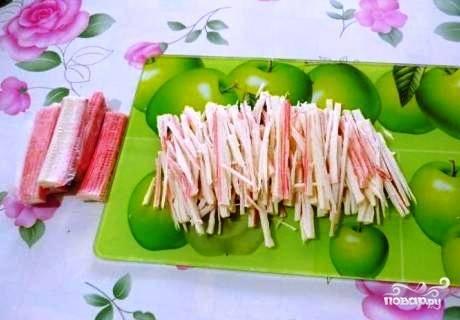 Крабовые палочки нарезаем соломкой.