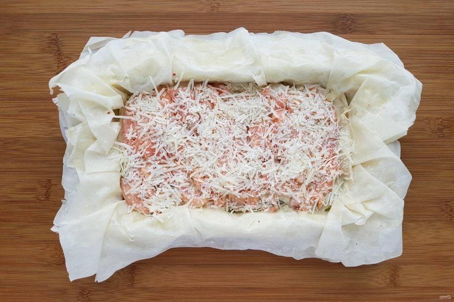 Снова возьмите два листа теста и смочив их в заливке выложите поверх лука. Сверху выложите оставшуюся часть рыбы. Посыпьте сыром.
