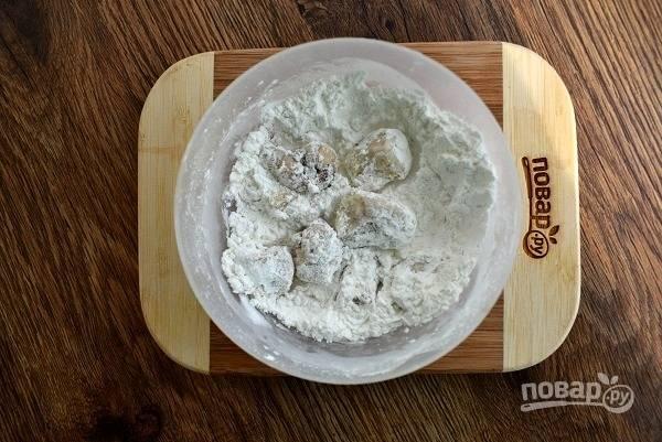 Масло налейте в сотейник (сковороду), нагрейте до 180°C. Слейте маринад, обваляйте кусочки курицы в крахмале.