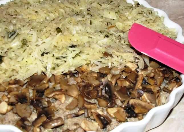 Смажьте форму маслом и выложите ингредиенты слоями: половина капусты, фарш, грибы и остальная капуста. Сверху залейте сметанным соусом и запекайте в духовке 20 минут при 200 градусах.
