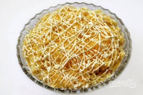 Сыр трем на мелкой терке, половину укладываем слоем после миндаля. Делаем сетку из майонеза, после чего снова повторяем слои.