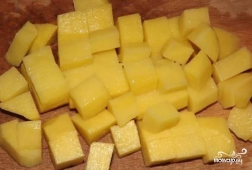 В кастрюлю наливаем воду и ставим на огонь, добавляем немного соли. Нарезаем картофель кубиками и выкладываем в кипящую воду.