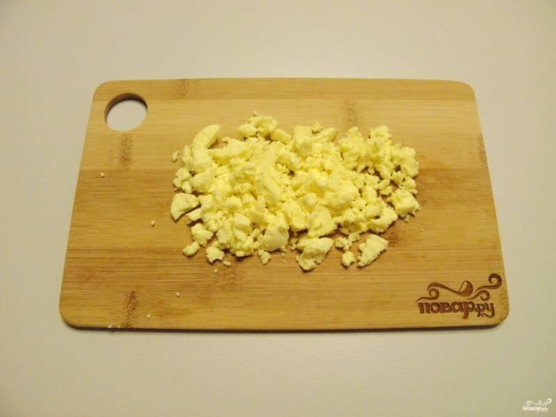 Отваренные яйца остудите, очистите. Отделите белки от желтков. Желтки порубите ножом.