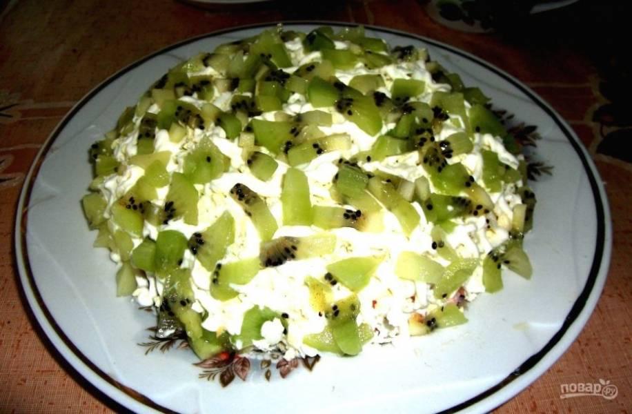В конце нарежьте кусочками киви. Украсьте ими салат. Перед подачей оставьте блюдо в холодильнике. Приятного аппетита!
