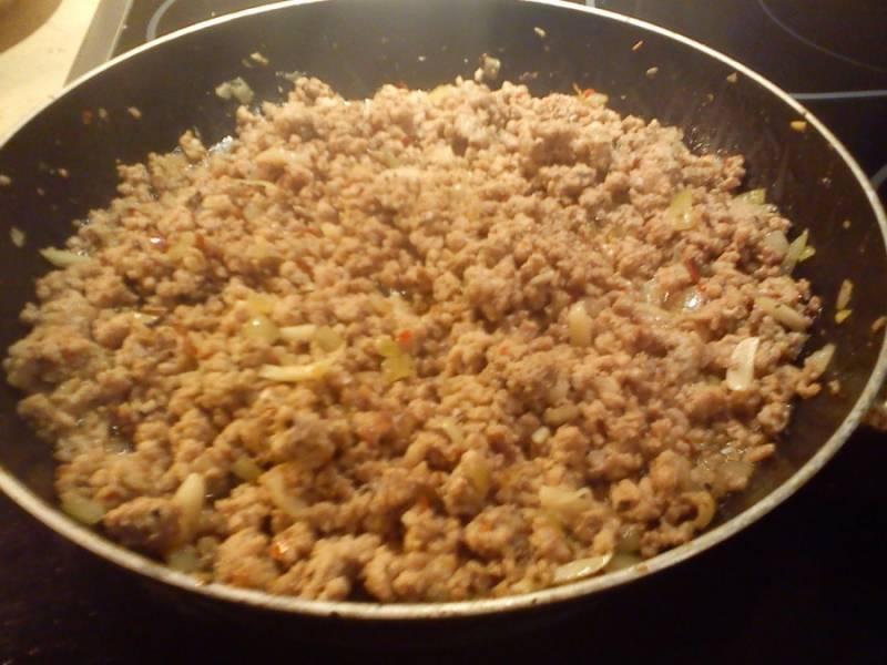 На сковороде на разогретом масле поджарьте мелко нарезанный лук, добавьте фарш, соль, перец, розмарин, петрушку и, постоянно перемешивая, поджарьте.