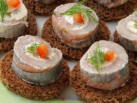 9. Выложить рулет на ломтик хлеба и украсить зеленью, помидорчиком или перцем, например. Вот и весь простой рецепт рулета из селедки.