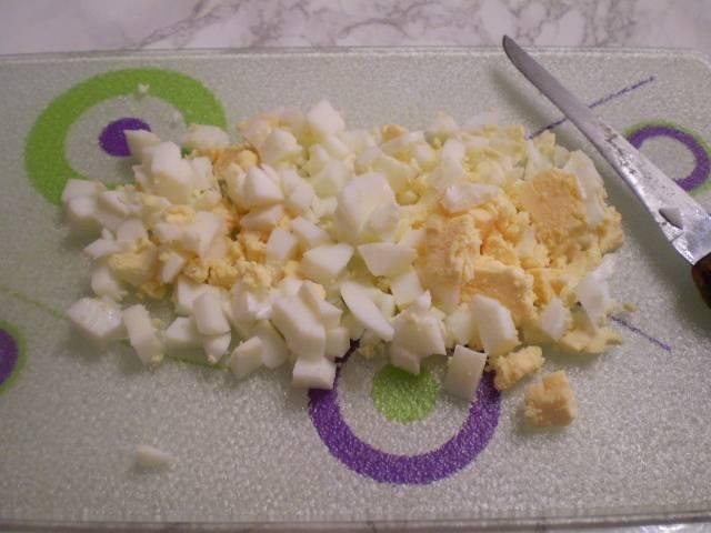 Порежьте кубиками яйца.