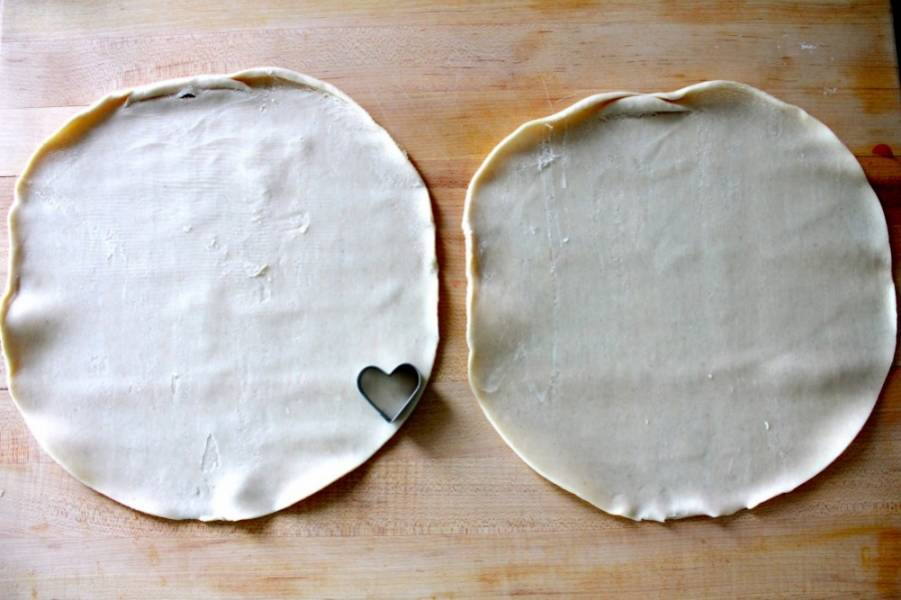 2. Вторую часть теста нужно немного раскатать. В данном случае при приготовлении клубничного пирога из слоеного теста используется выемка сердечком, но можно взять и любую другую для украшения.