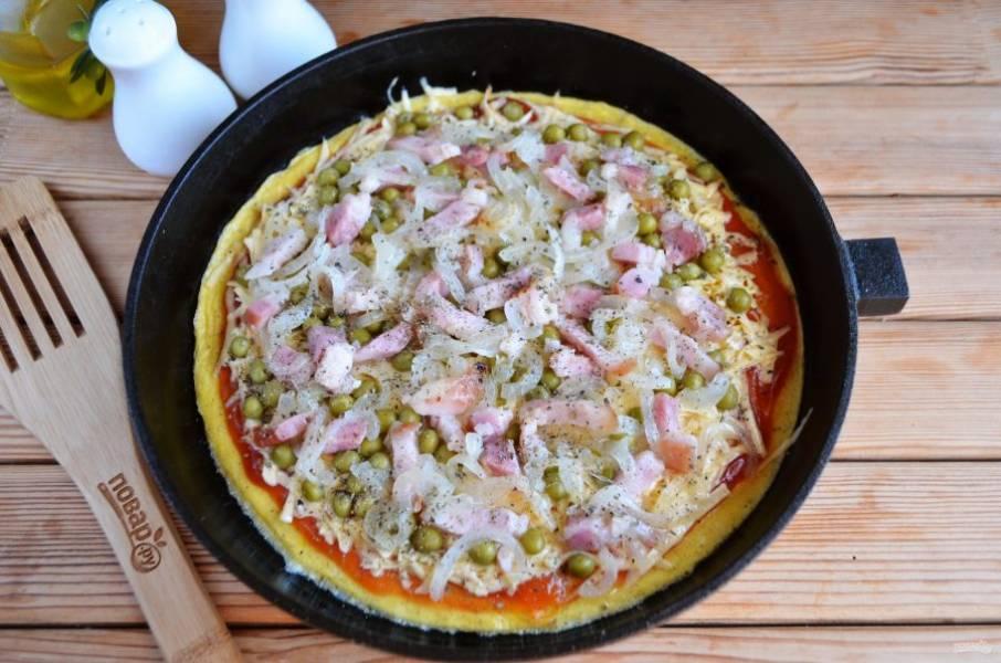 Сверху положите лук, бекон, добавьте орегано. Отправьте пиццу в духовку на 10-15 минут, температура — 180 градусов.