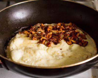 7. Омлет можно жарить на отдельной сковороде или той, в которой были грибочки, предварительно сняв их и переложив. На среднем огне омлет необходимо довести до готовности под крышкой. При желании можно перевернуть его аккуратно. Когда яйца как следует прожарились, на одну половину выложить начинку. Осталось только свернуть пополам и омлет с лисичками в домашних условиях готов. Подавать блюдо можно с овощами и свежей зеленью.