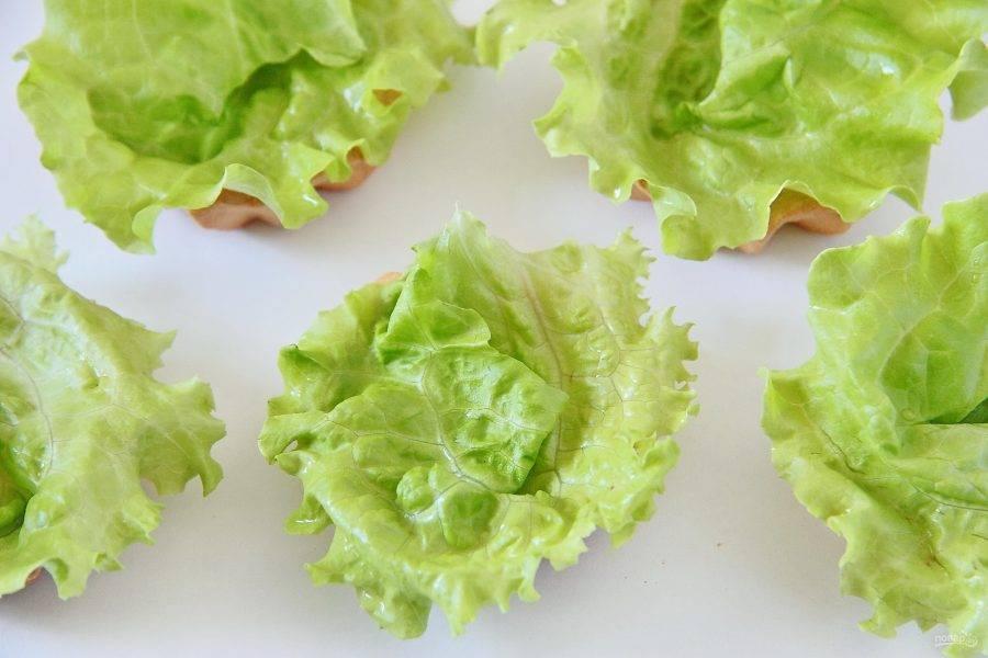 Уложите на дно тарталеток листик салата так, чтобы он немного выглядывал из верхней части корзиночек.