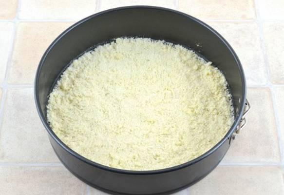 Смазываем форму для выпечки маслом. Выкладываем в форму половину песочной крошки, разравниваем.
