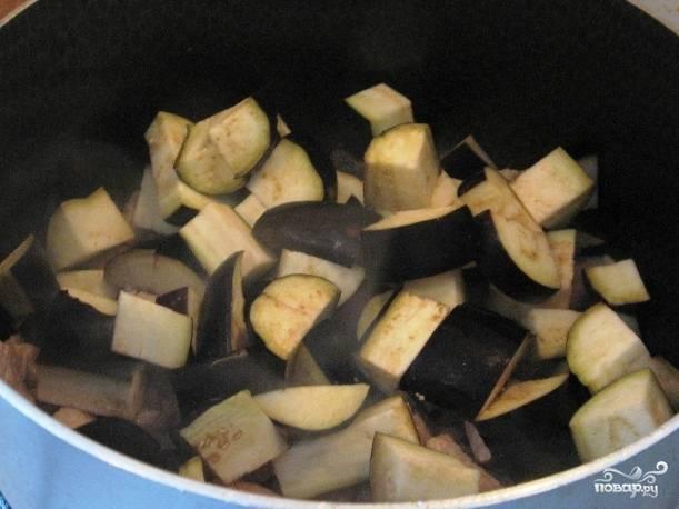 Нарезаем баклажаны, отправляем их к обжаренному мясу и слегка солим. Закрываем сковороду крышкой минут на 5-7, пусть баклажаны дадут сок.