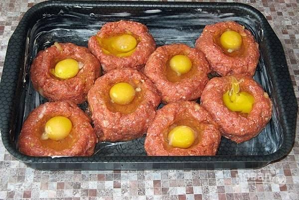 7. Сформируйте из фарша шарики, выложите их в форму, сделайте в центре углубление. Аккуратно вбейте яйцо. Отправьте форму в разогретую до 200 градусов духовку.