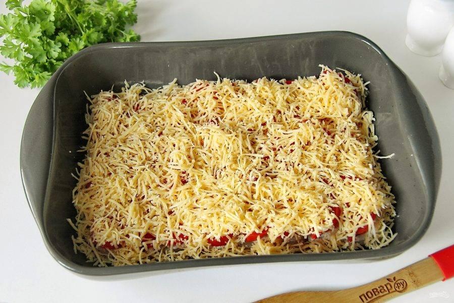 Рыбу с помидорами равномерно посыпьте тертым сыром. Готовьте в духовке при температуре 180 градусов около 30 минут.