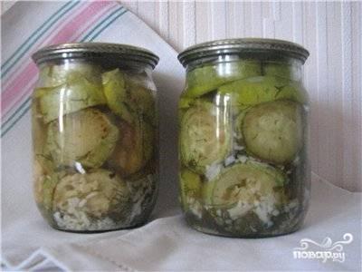 Кабачки уложить в чистые банки, перекладывая зеленью и чесноком, залить маслом с уксусом, пастерезовать и закатать.