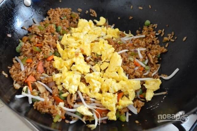Теперь влейте соевый соус, добавьте ростки и яйца, перемешайте и прогрейте все минутку. По вкусу добавьте соль и белый перец.