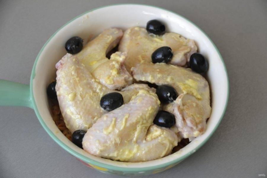 Выложите обжаренные крылышки на макароны, уложите сверху оливки или маслины.