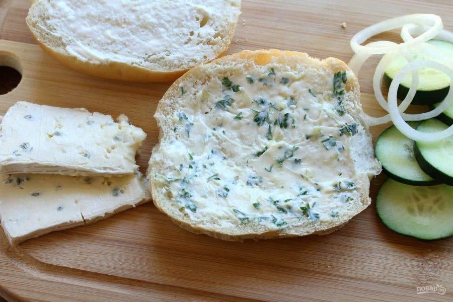 5.Разрежьте булку на 2 части, смажьте одну чесночным маслом с зеленью, выложите кольца огурчика, затем лук, уложите ломтики сыра. Вторую часть булки смажьте майонезом и накройте сэндвич, разрежьте его на 2 части. Проделайте все действия со второй булкой.