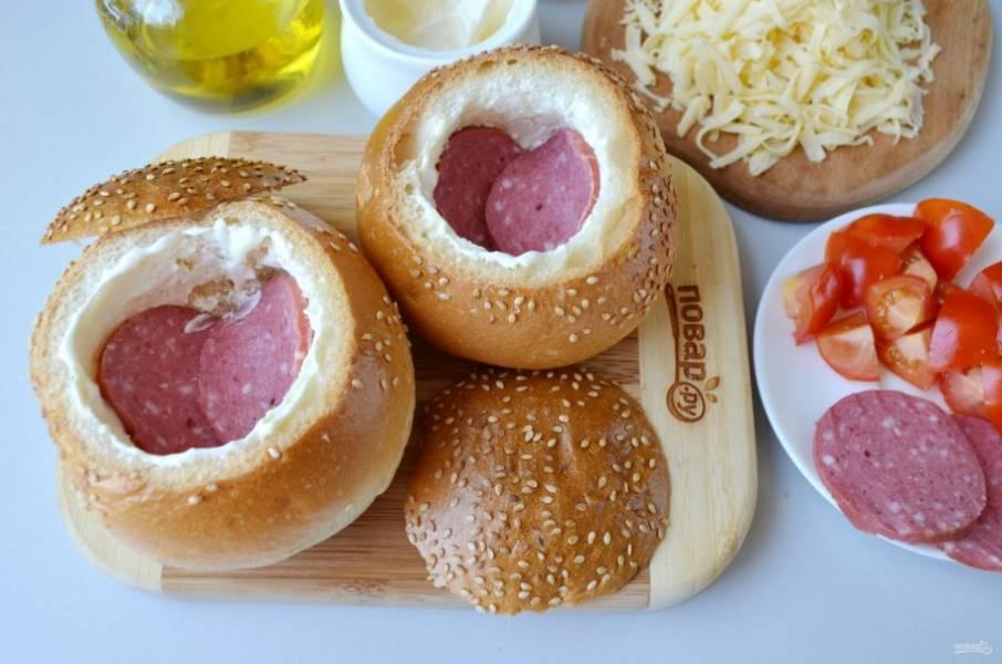 Смажьте булочки внутри майонезом или другим соусом, сметаной. Положите по несколько колечек колбаски на самое донышко.