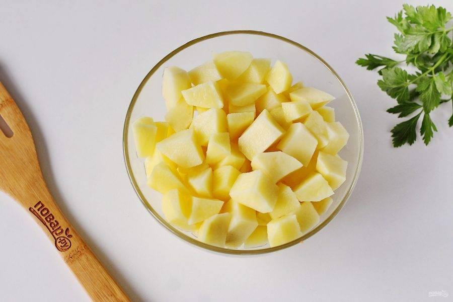 Тем временем картофель очистите и нарежьте кубиками.