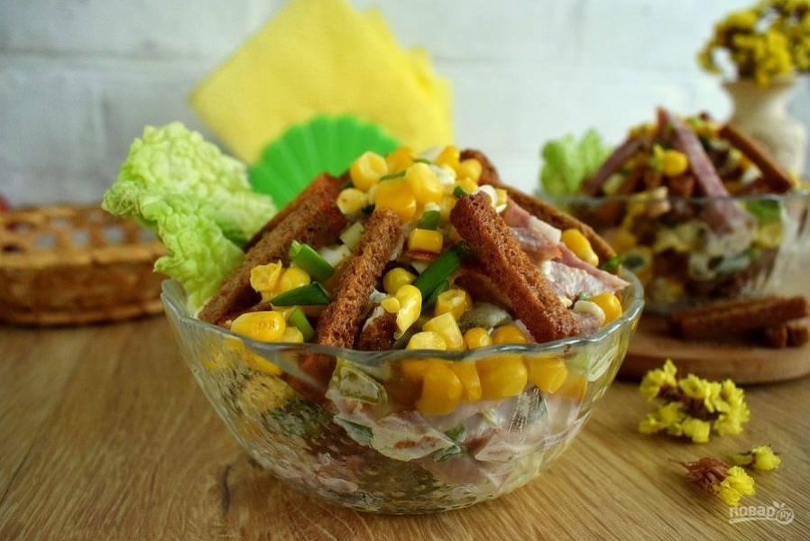 Зеленый лук измельчите. Смешайте все ингредиенты с майонезом, дайте немного пропитаться. Выложите часть сухариков и кукурузы для украшения.