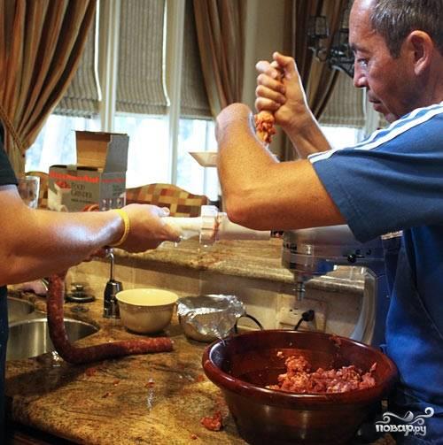 Шаг 4. Лучше всего формировать колбаски, работая в паре с помощником, один загружает мясо в мясорубку, второй контролирует его поступление и продвижение по кишке. Завяжите кишку в узел с одной стороны. Наполняйте ее фаршем плотно, чтобы оставалось как можно меньше воздуха.  Оставьте в конце кишки пустое место (где-то 7-10 см.), максимально туго завяжите конец.