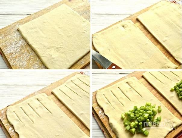 4. Слоеное тесто выложите на рабочий стол, раскатайте немного и нарежьте небольшими прямоугольниками. С одного края сделайте небольшие надрезы для выхода пара. На второй край выложите начинку.