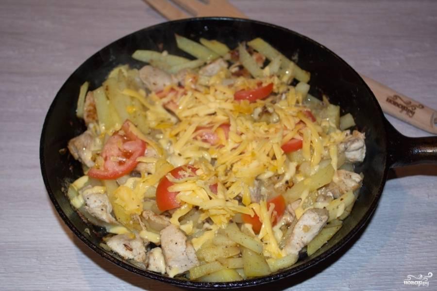 Когда картофель будет готов, сверху выложите дольки помидоров. Посыпьте натертым твердым сыром. Закройте сковороду крышкой и дайте 5 минут пропариться. Жар растопит сыр.