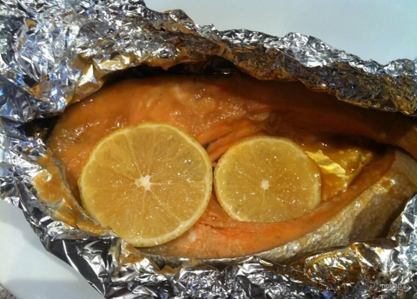 4.Готовую рыбу достаю из духовки, разворачиваю фольгу и кладу по 2 ломтика лимона на каждый кусочек.