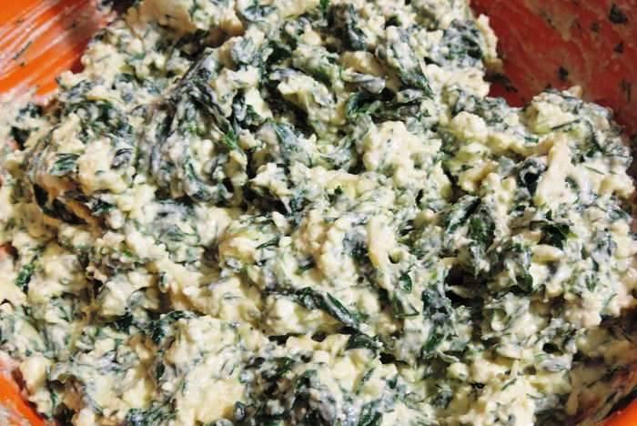 Шпинат, петрушку и укроп мелко нарежьте, добавьте творог, сметану и два трети тертого сыра. Хорошо перемешайте.