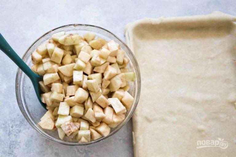4.Достаньте форму с тестом из холодильника, выложите яблоки в один слой.