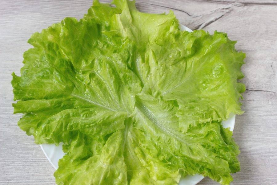 Листья салата помойте, немного обсушите и выложите на блюдо.