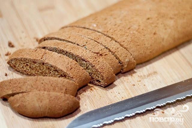 4. Выпекать около 30 минут, до золотисто-коричневого цвета и появления трещин на поверхности. Убрать из духовки и дать остыть в течение 10 минут. Снизить температуру духовки до 160 градусов. Поместить оба хлеба на разделочную доску и нарезать на ломтики по диагонали около 1 см толщиной.