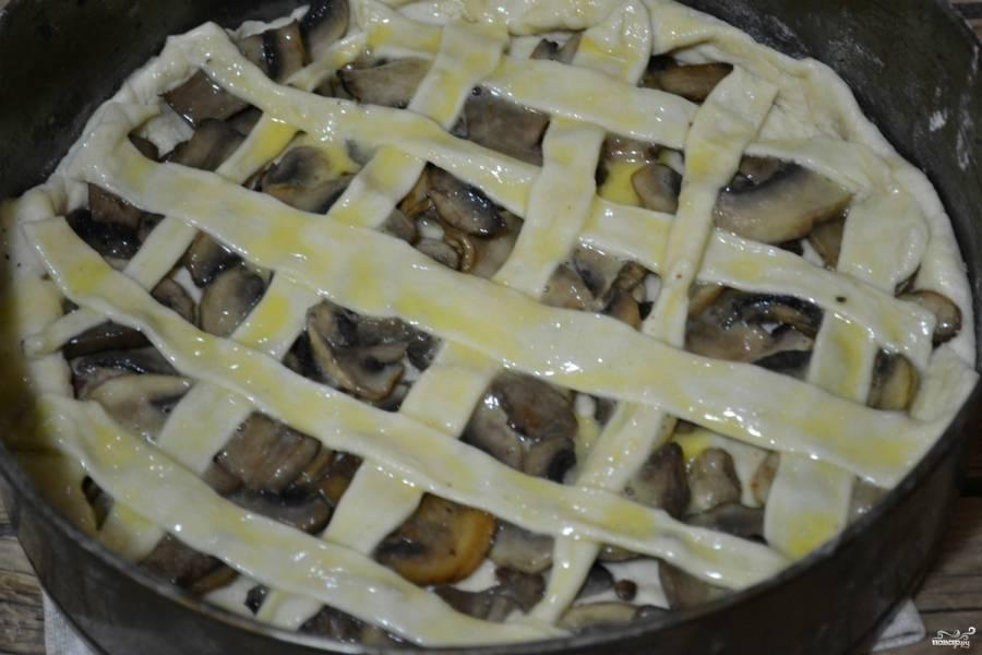 Оставшееся тесто тонко раскатайте и порежьте на полоски. Сделайте из этих полосок сеточку на пироге, смажьте ее взбитым яйцом. Отправьте пирог в разогретую духовку на 25 минут.