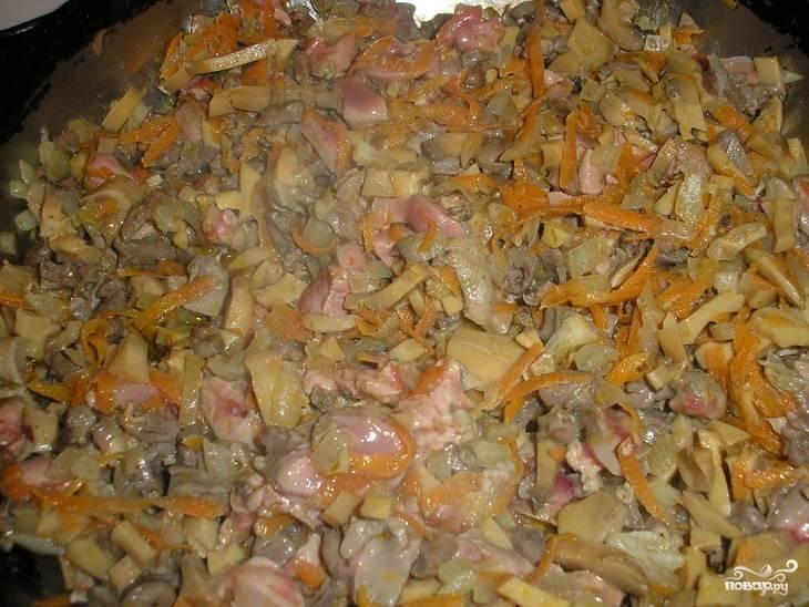 Очистите лук и морковь. Нарежьте лук, а морковь натрите на крупной тёрке. Начинайте обжаривать овощи на растительном масле. Тем временем вымойте и некрупно нарежьте сердца и печень. Обжарьте мясо на сковороде до полуготовности. Затем вымойте и нарежьте шампиньоны, отправьте их на сквороду и обжарьте.