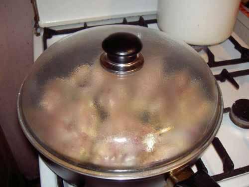 Когда выложили курицу, накрываем сковородку крышкой. Готовим до покраснения.