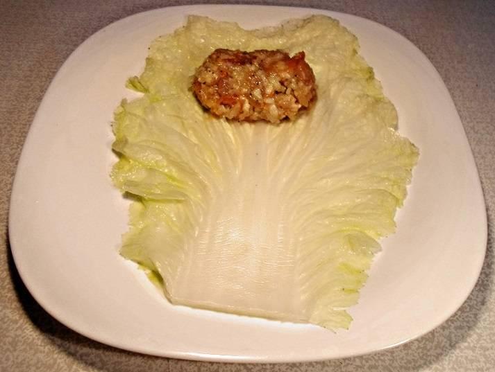 Выложите на тарелку один лист капусты, расправьте, а на него положите немного начинки.