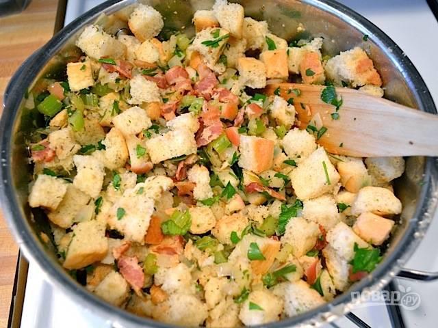 7.Добавьте кубики хлеба вместе с крошками и порезанной петрушкой в сковороду к овощам, все тщательно перемешайте.