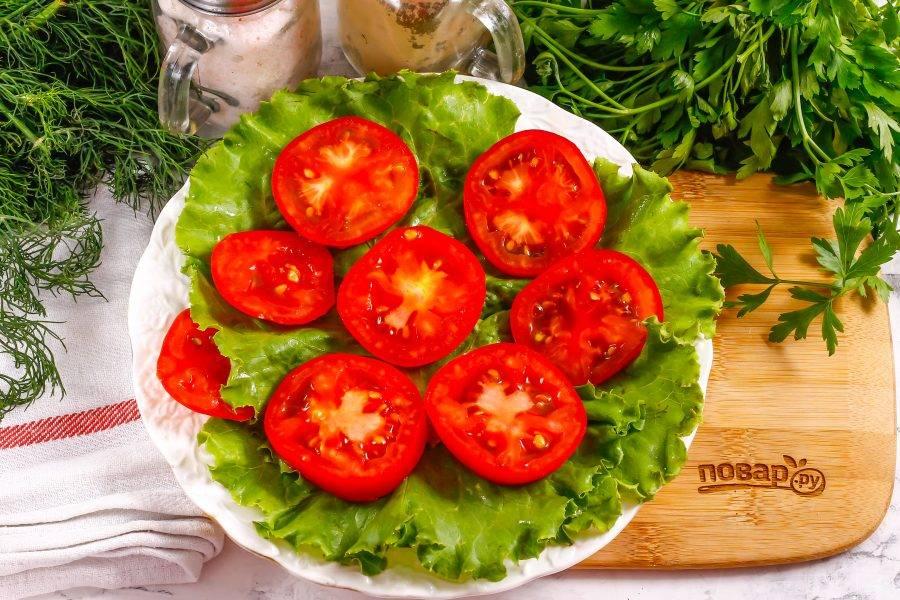 Промойте помидоры в воде, срежьте зеленые сердцевинки, нарежьте их кольцами и выложите на листья салата.