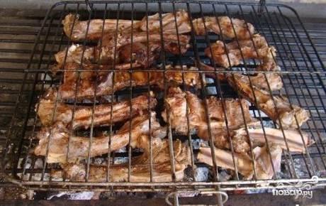 5.Промариновавшиеся ребрышки выкладываем на решетку. Разравниваем в мангале угли, затем кладем решетку с ребрышками на мангал. Главный секрет приготовления баранины на углях – медленное обжаривание мяса на слабом огне. Если готовить бараньи ребрышки на сильном жаре, они получатся жестким. Готовим ребрышки 40-60 минут на слабом огне, периодически переворачивая решетку.