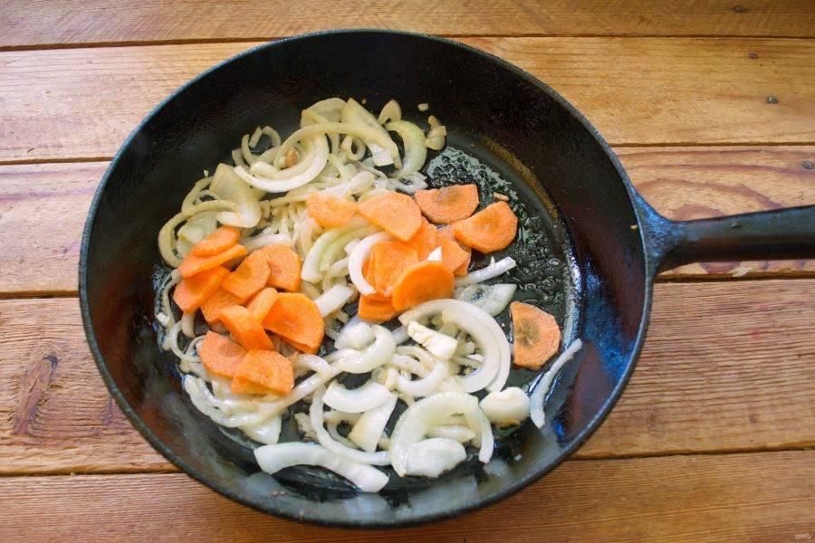 В другой сковороде на растительном масле обжарьте нарезанный репчатый лук. Добавьте нарезанную морковь.