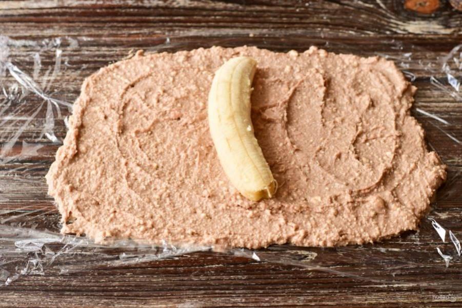 На стол выложите пищевую пленку, а на нее творожную массу. В центр выложите банан.