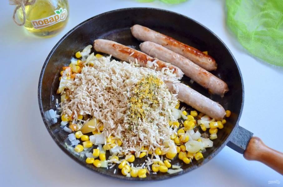 Колбаски и овощи подрумянились. Доводить до полной готовности их не нужно, они будут еще вариться с рисом. Добавьте рис, специи.