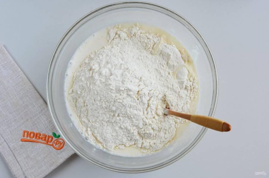 Всыпьте большую половину муки в тесто, начните замешивать ложкой.