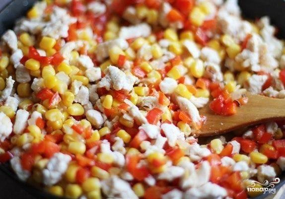 Добавляем к куриному филе поджаренные перец, лук и чеснок, а также кукурузу. Хорошенько перемешиваем, добавляем тмин и обжариваем еще 5-7 минут на среднем огне.