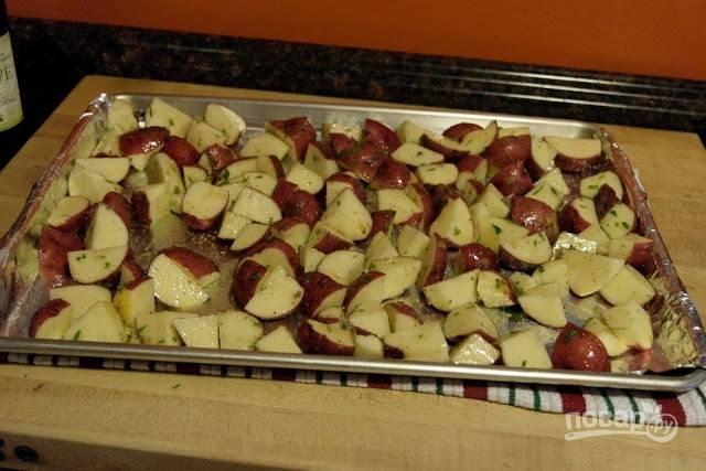5. Теперь картофель можно выложить на противень и отправить в разогретую до 190 градусов духовку. Запекайте минут 15, после аккуратно перемешайте и оставьте в духовке еще минут на 15.